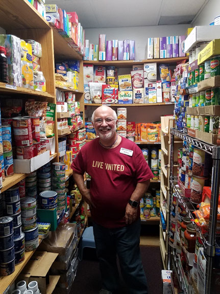 smiling man in walk-in pantry full of food